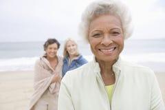 Femme supérieure dans la veste d'ouatine avec des amis sur la plage Images stock
