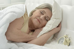 Femme supérieure dans le lit Images stock