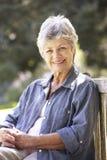Femme supérieure détendant sur le banc de parc Images stock