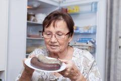 Femme supérieure heureuse tenant le plat avec des saucisses de foie de porc Photographie stock libre de droits
