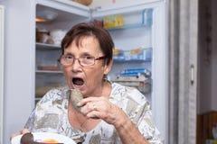 Femme supérieure mangeant la saucisse de foie de porc Image stock