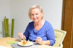 Femme supérieure mangeant un repas Photographie stock
