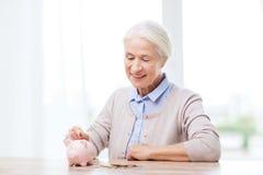 Femme supérieure mettant l'argent à la tirelire à la maison Photos stock