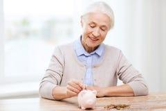 Femme supérieure mettant l'argent à la tirelire à la maison Photo stock