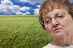 Femme supérieure mélancolique avec le champ d'herbe derrière Photos libres de droits
