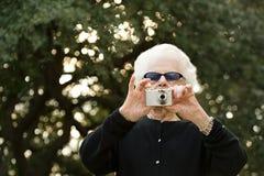 Femme supérieure prenant une photographie Photo stock