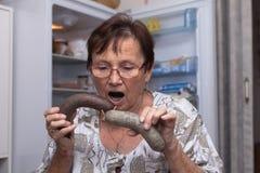 Femme supérieure étonnée tenant des saucisses de foie de porc Photographie stock libre de droits