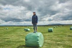 Femme sur des balles de foin dans un domaine Photos stock