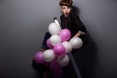 Femme sur l'échelle d'opération avec des ballons à air ayant l'amusement Image stock