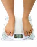 Femme sur l'échelle de poids Photo stock