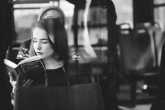 Femme sur l'autobus lisant un livre Photos stock