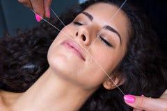 Femme sur l'enlèvement de pilosité faciale filetant la procédure Photographie stock libre de droits