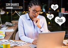 Femme sur l'ordinateur portable avec des actions et des barres de statut de goûts Photographie stock libre de droits