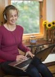 Femme sur l'ordinateur portatif dans la cuisine Image libre de droits