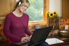 Femme sur l'ordinateur portatif dans la cuisine Image stock