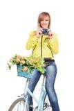 Femme sur la bicyclette avec l'appareil-photo de film de vintage Photos stock
