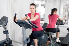 Femme sur la bicyclette d'exercice Image libre de droits