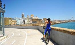 Femme sur la bicyclette, vue panoramique de Cadix avec la cathédrale, Andalousie, Espagne Image stock