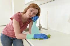 Femme sur la cuisine avec le tissu de lavage en caoutchouc de gants et le nettoyage de détergent ennuyés et fatigués photo libre de droits