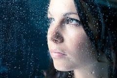 Femme sur la fenêtre sous la pluie Photos stock