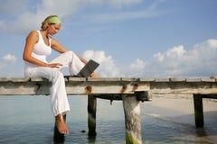 Femme sur la jetée avec l'ordinateur portatif