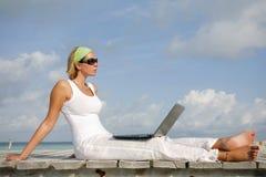 Femme sur la jetée avec l'ordinateur portatif Photos stock