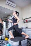 Femme sur la machine d'avion-école en gymnastique de sport Images stock