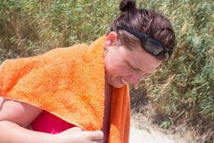 Femme sur la plage avec une serviette Image stock