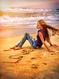 Femme sur la plage dans l'amour d'écriture de coucher du soleil sur le sable Photo stock