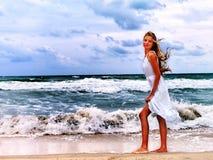 Femme sur la plage dans l'amour d'écriture de coucher du soleil sur le sable Photographie stock