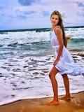 Femme sur la plage dans l'amour d'écriture de coucher du soleil sur le sable Images stock
