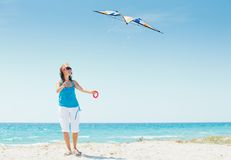 Femme sur la plage jouant avec un cerf-volant coloré Photos libres de droits