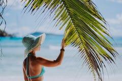 Femme sur la plage touchant l'ombre de feuille de palmier utilisant le chapeau bleu Concept de luxe de vacances de récréation de  photos stock