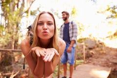 Femme sur la promenade avec le baiser de soufflement de l'homme à l'appareil-photo Image stock