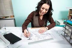 Femme sur le bureau fonctionnant avec des modèles dans l'avant Images stock