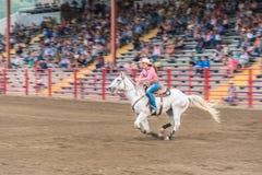 Femme sur le cheval blanc galopant à la grande vitesse au baril emballant la concurrence Photographie stock libre de droits