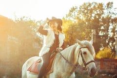 Femme sur le cheval dans le chapeau Photo stock