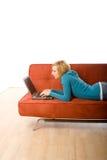 Femme sur le divan avec l'ordinateur portatif Photographie stock