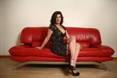 Femme sur le divan rouge Photos stock