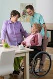 Femme sur le fauteuil roulant, l'ami et l'infirmière Image stock