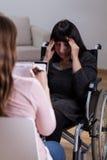 Femme sur le fauteuil roulant parlant avec le thérapeute images libres de droits