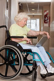 Femme sur le fauteuil roulant utilisant l'ordinateur portable Photographie stock libre de droits