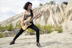 Femme sur le fond arénacé avec la guitare basse Image libre de droits
