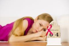 Femme sur le lit, jour de cancer du sein du monde sur le calendrier Photographie stock libre de droits