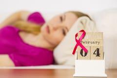 Femme sur le lit, jour de cancer du sein du monde sur le calendrier Images libres de droits