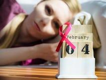 Femme sur le lit, jour de cancer du sein du monde sur le calendrier Photographie stock