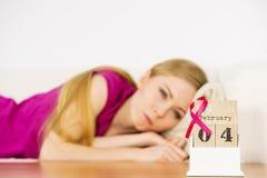 Femme sur le lit, jour de cancer du sein du monde sur le calendrier Image libre de droits