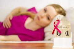 Femme sur le lit, jour de cancer du sein du monde sur le calendrier Image stock