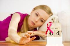 Femme sur le lit, jour de cancer du sein du monde sur le calendrier Photos libres de droits