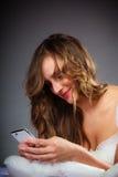 Femme sur le lit tenant le téléphone portable Photos stock